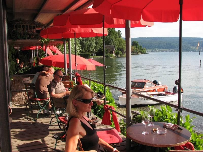 Restaurant am Campingplatz Sandseele/Menschen unter roten Sonnenschirmen und Motorboote im Hintergrund - © Campingplatz Sandseele GmbH