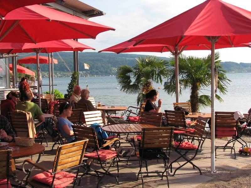 Restaurant am Campingplatz Sandseele/Menschen unter roten Sonnenschirmen - © Campingplatz Sandseele GmbH